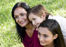 Woman sitting on the grass with her two daughters