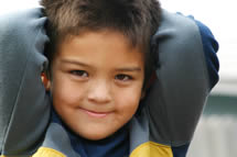 A boy smiling with his hands behind his head