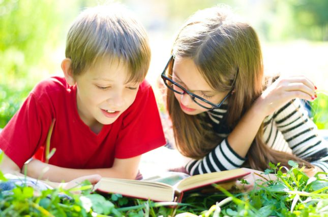 A Boy And A Girl Laying On The Grass Reading A Book
