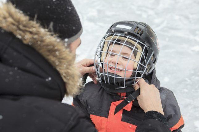 A man helping his son with his hockey helmet