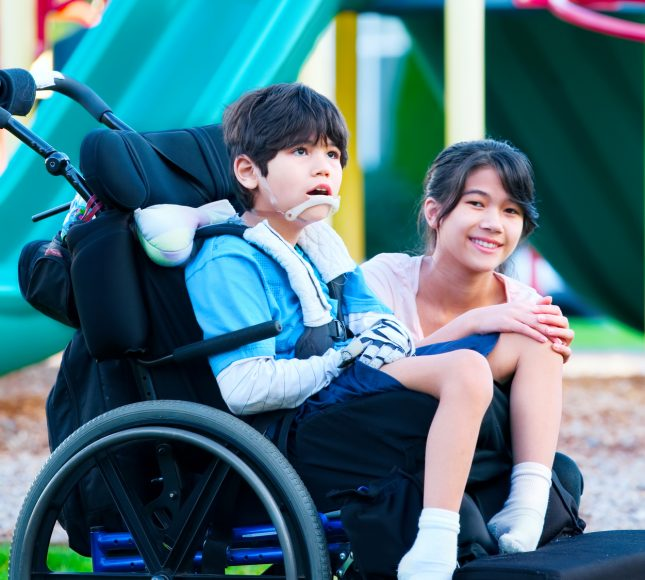 Girl sitting next to her brother, in a wheelchair
