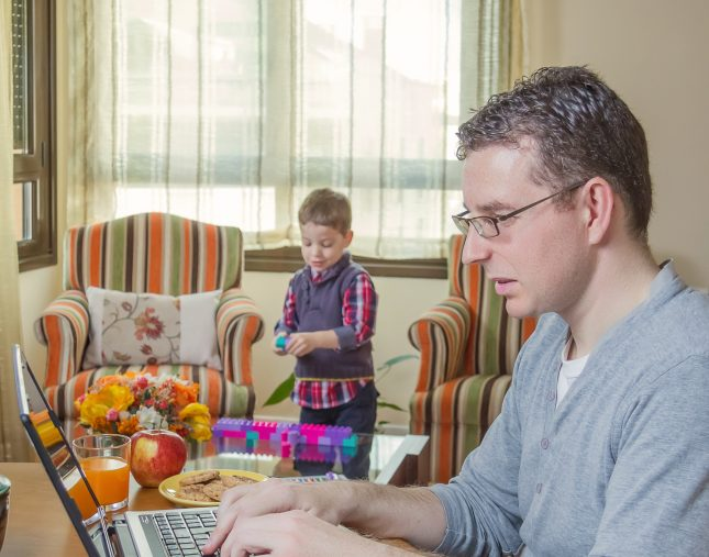 Man working at laptop with son playing in the background