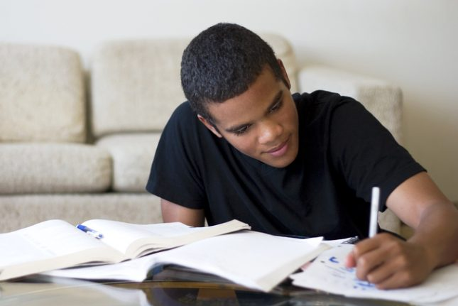 Teen doing homework on a coffee table