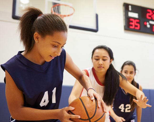 Teenage female basketball game in high school gym