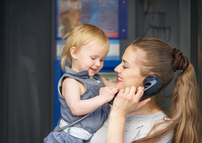 Woman Holding Her Daughter While Talking On The Phone